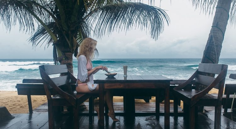 girl sitting on a bench at a table on the beach and eating
